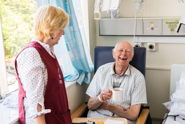 A refreshments volunteer laughing with a patient