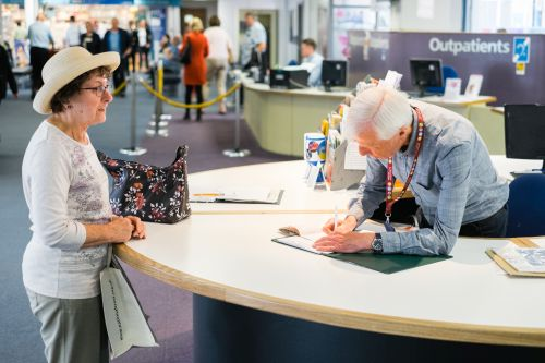 A volunteer and hospital visitor at the hospital reception desk