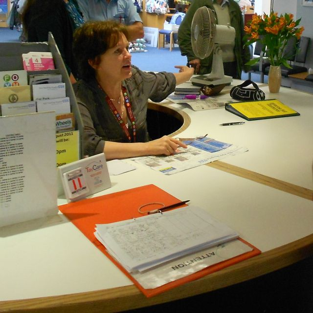 A volunteer at the reception desk giving directions