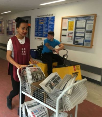 A volunteer with a newspaper trolley